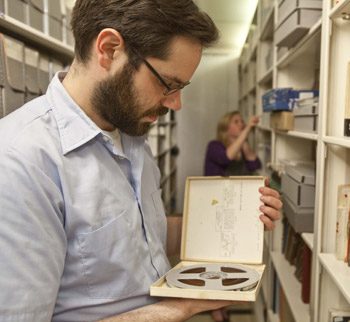 David Shlitt, a fellow of the Yiddish Book Center in Amherst, Mass., examines a tape in the Jewish Public Library archives. [Michael Carroll photo]
